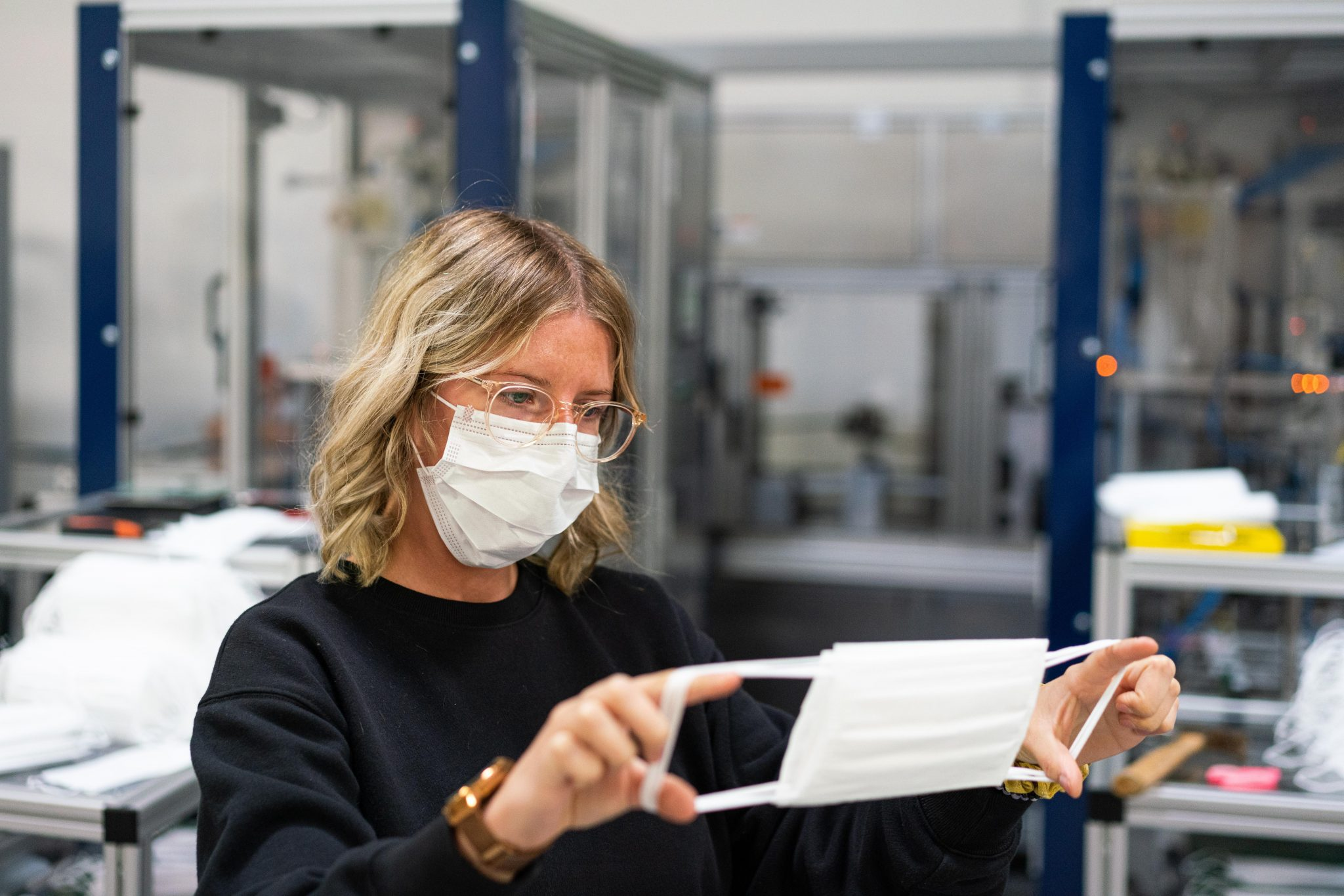 woman in a white mask examining a mask to see if its see through